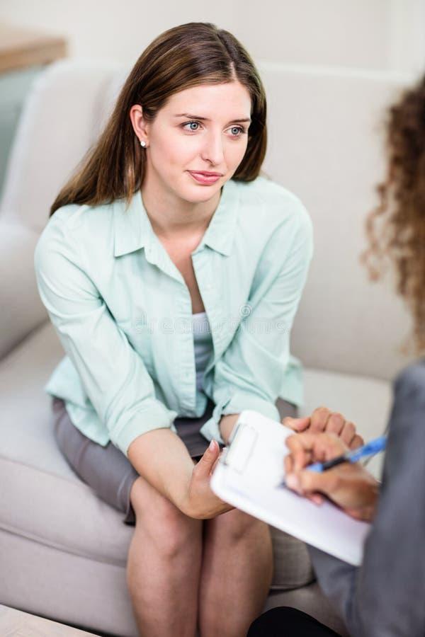 Schöne junge Frau, die mit Psychologen sich bespricht lizenzfreie stockbilder