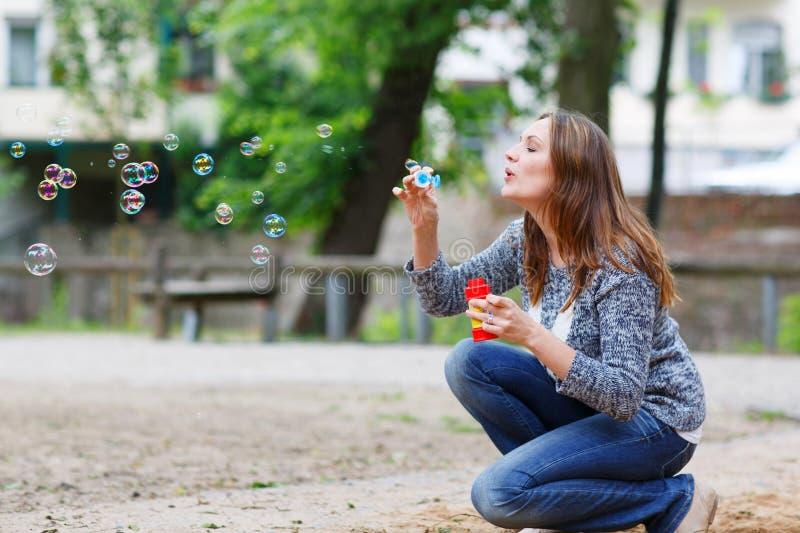 Schöne junge Frau, die mit Seifenblasen im Park spielt stockfotografie