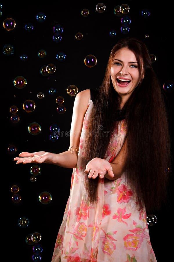 Schöne junge Frau, die mit Seifenblasen spielt lizenzfreie stockfotografie