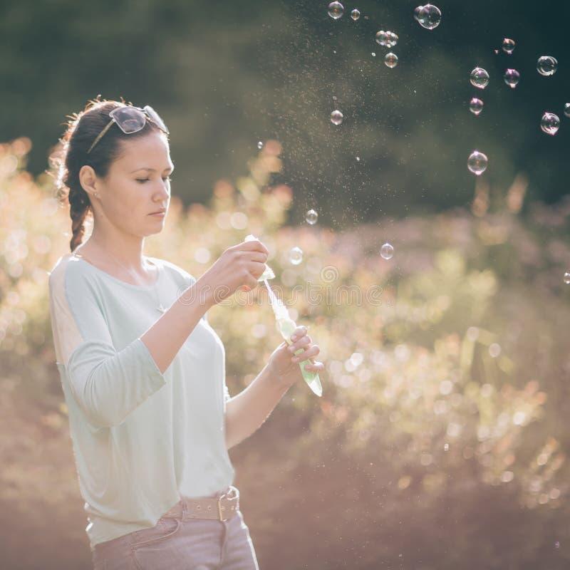 Schöne junge Frau, die mit Seifenblasen in Sunny Park spielt lizenzfreies stockbild