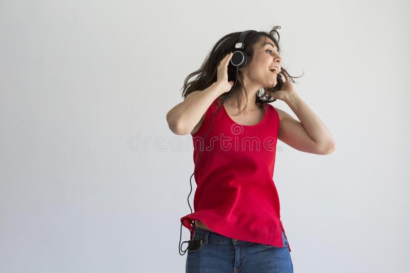 Schöne junge Frau, die Musik an ihrem Handy mit Kopfhörer hört und Spaß über weißem Hintergrund hat Beiläufige Kleidung stockbild