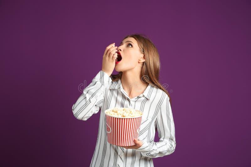 Schöne junge Frau, die Popcorn auf Farbhintergrund isst lizenzfreie stockbilder