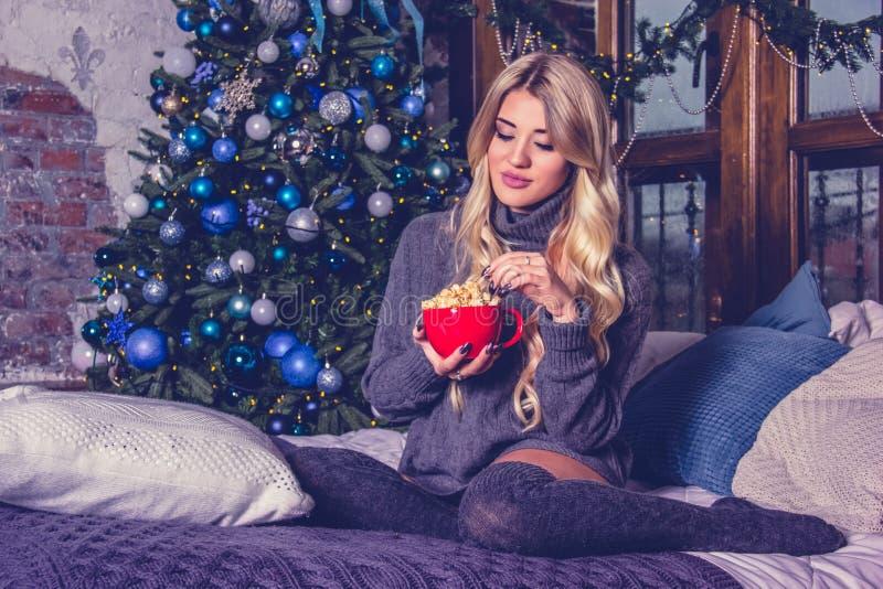 Schöne junge Frau, die Popcorn isst Schöne junge Frau in der gemütlichen Hauptkleidung zu Hause Weihnachten und neues Jahr lizenzfreie stockbilder