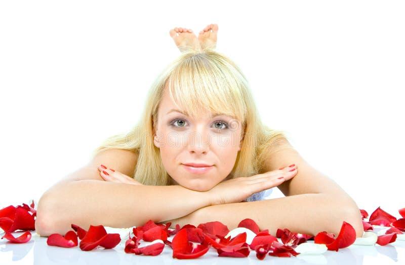 Schöne junge Frau, die rosafarbene Blumenblätter wirft lizenzfreies stockbild