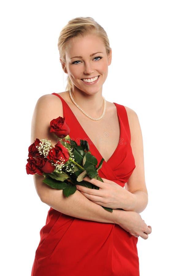 Schöne junge Frau, die rote Rosen anhält lizenzfreies stockbild