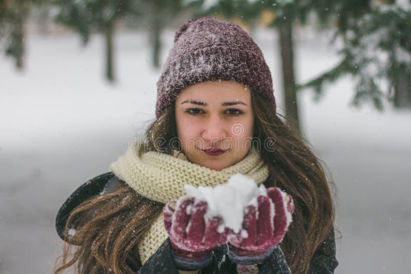 Schöne junge Frau, die Schnee in den Handschuhen hält Genießen der Natur stockfotos