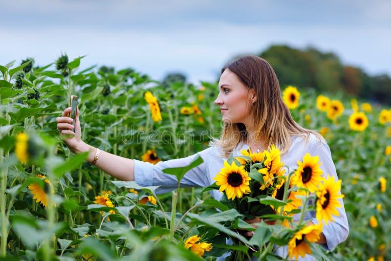 Schöne junge Frau, die selfie mit Smartphone auf Sonnenblumenfeld mit Blumenstraußblumen macht Glückliches Mädchen auf Sommersonn stockfotografie