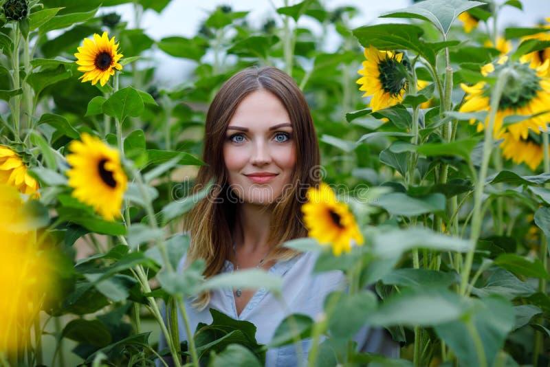 Schöne junge Frau, die selfie mit Smartphone auf Sonnenblumenfeld mit Blumenstraußblumen macht Glückliches Mädchen auf Sommersonn lizenzfreie stockfotografie