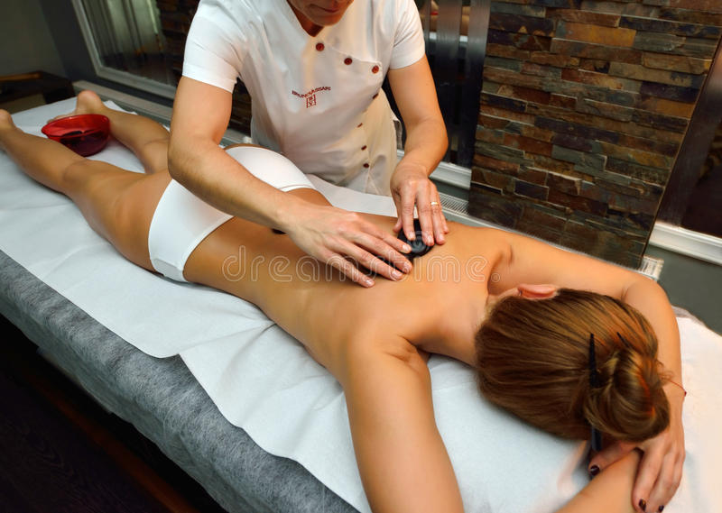 Schöne junge Frau, die sich auf Massagetabelle hinlegt lizenzfreie stockbilder