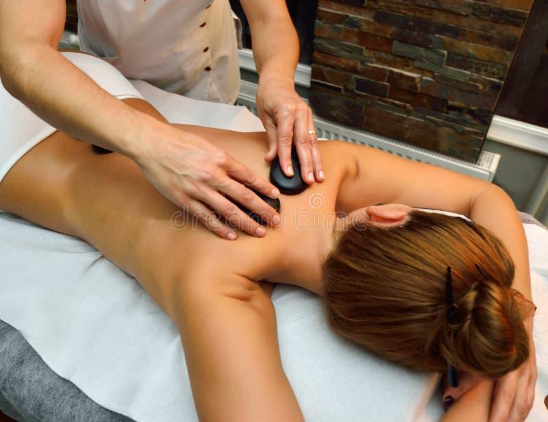 Schöne junge Frau, die sich hinlegt, während Massagetherapeut mas ist lizenzfreie stockfotos