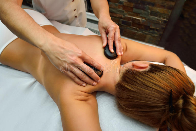 Schöne junge Frau, die sich hinlegt, während Massagetherapeut mas ist stockfoto