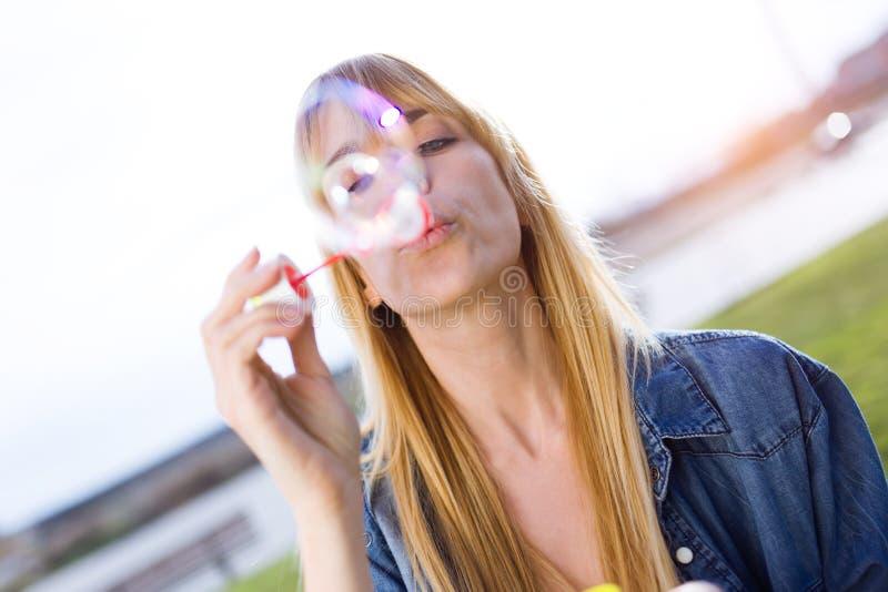 Schöne junge Frau, die Spaß mit Seifenblasen im Park hat lizenzfreies stockfoto