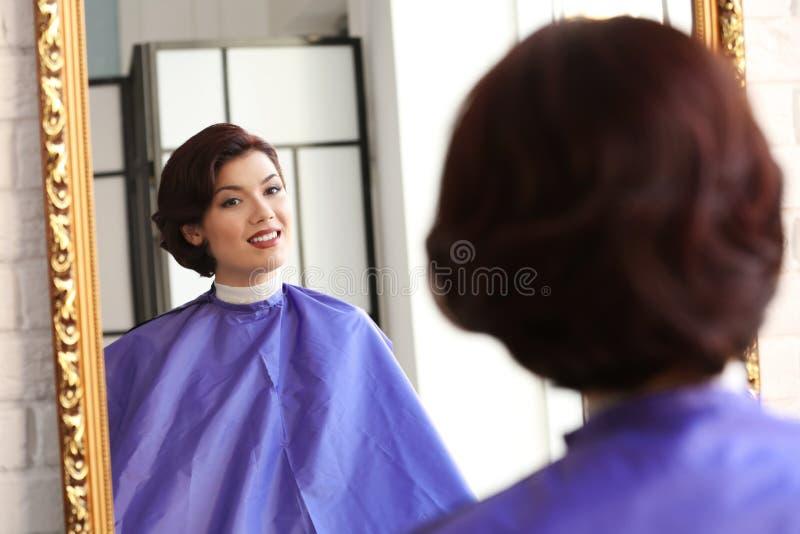 Schöne junge Frau, die Spiegel betrachtet lizenzfreies stockbild