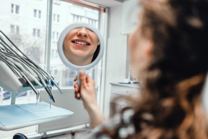 Schöne junge Frau, die Spiegel mit Lächeln im Büro des Zahnarztes s betrachtet stockfotografie