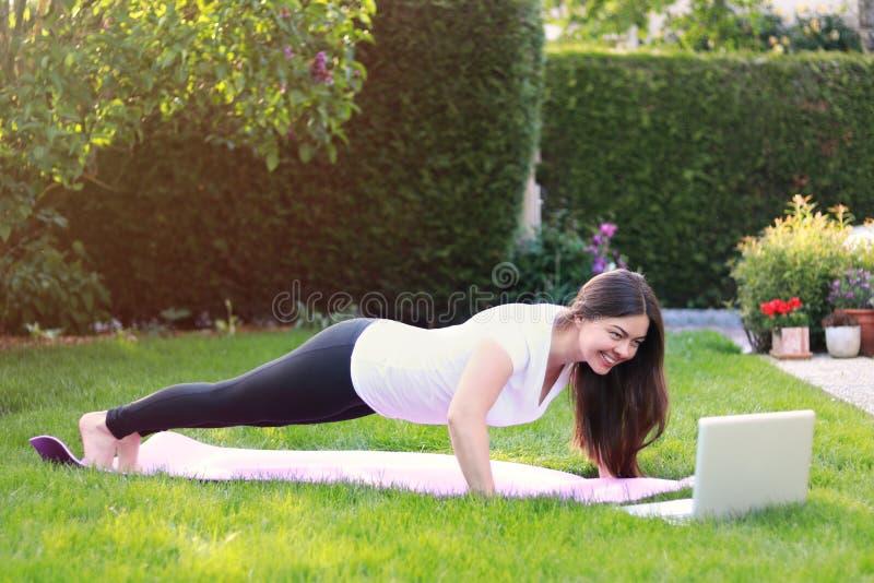 Schöne junge Frau, die Sport in ihrem Garten draußen folgt Führer des Online-Tutorials oder Trainer auf Laptop tut Gesundes lifes stockfotografie