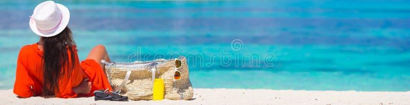 Schöne junge Frau, die am Strand sich entspannt stockbild