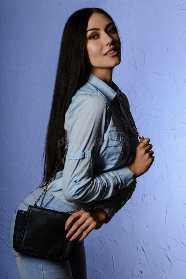 Schöne junge Frau, die an studioin Jeans mit Tasche aufwirft lizenzfreie stockfotografie