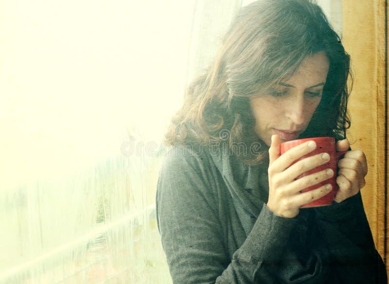Schöne junge Frau, die Tasse Kaffee genießt stockbilder