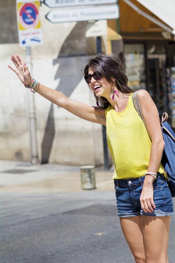 Schöne junge Frau, die Taxi auf der Straße ruft stockbilder
