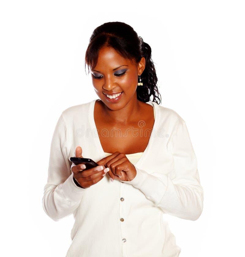 Schöne junge Frau, die um schwarzes Mobiltelefon ersucht lizenzfreie stockfotografie