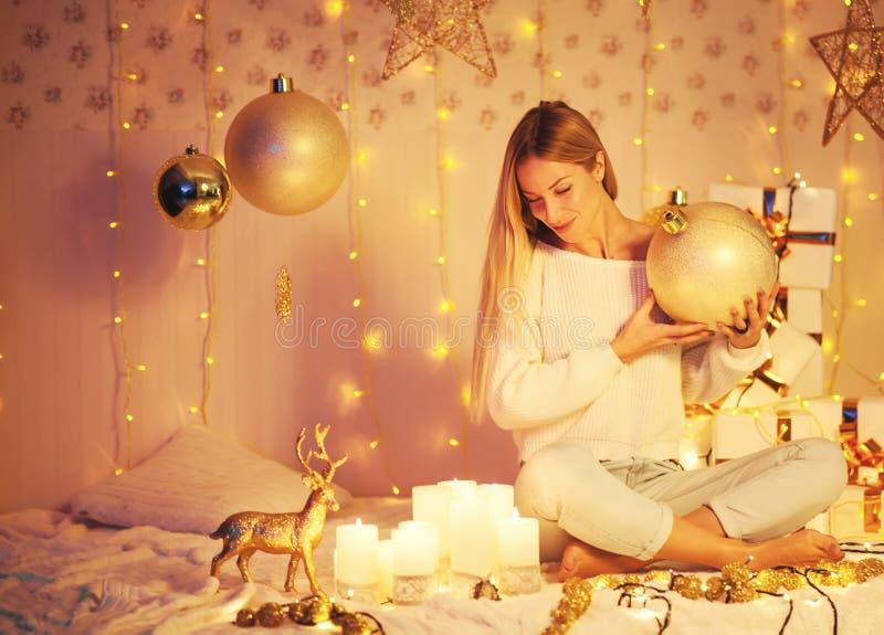Schöne junge Frau, die in verziertem Feiertagsraum mit Geschenkbällen auf Weihnachtshintergrund sitzt! Frohe Weihnachten stockfotografie