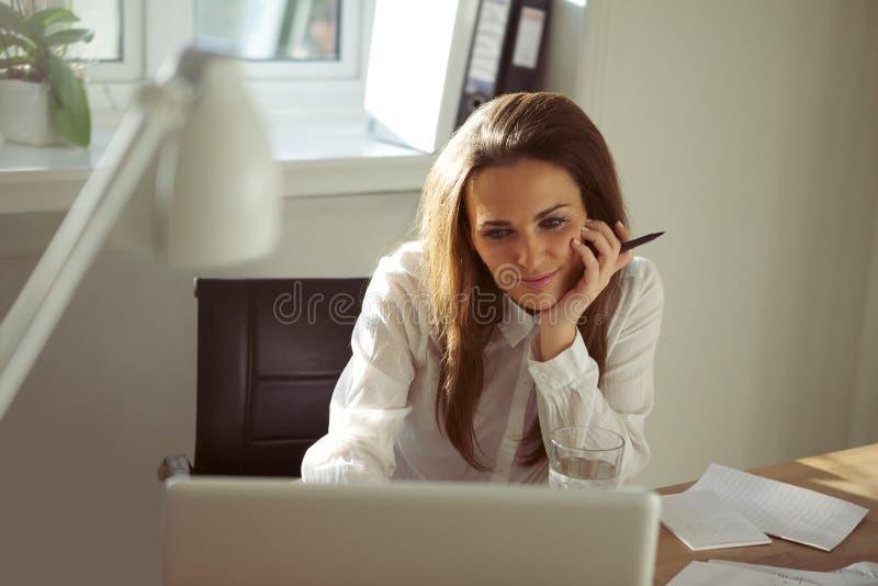 Schöne junge Frau, die vom Haus unter Verwendung des Laptops arbeitet lizenzfreies stockbild