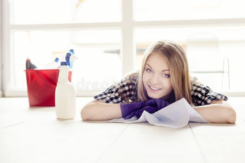 Schöne junge Frau, die während der Reinigung der Wohnung stillsteht stockfoto