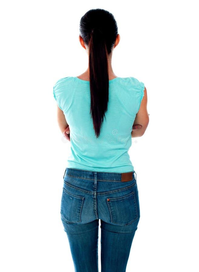 Schöne junge Frau, die Wand betrachtet. Hintere Ansicht lizenzfreie stockfotos