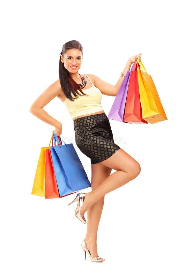 Schöne junge Frau, die wenige Einkaufstaschen hält stockbilder