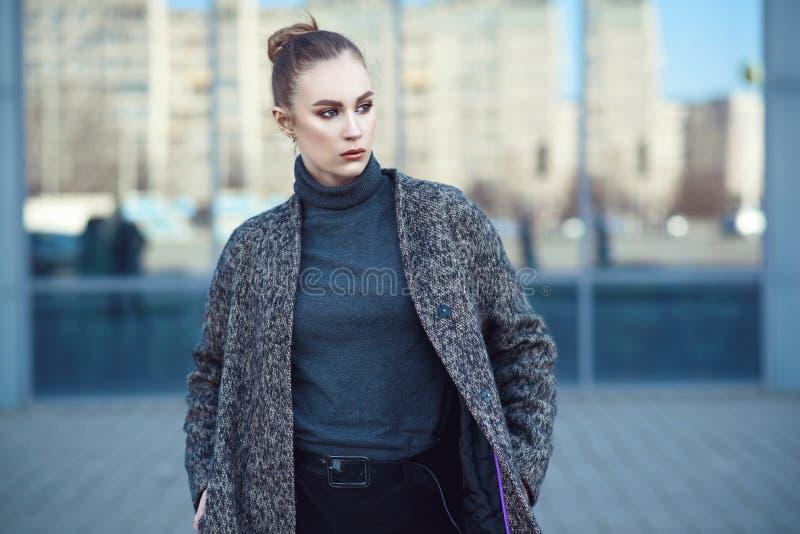 Schöne junge Frau, die am widergespiegelten Fenster des Stadtmalls geht stockfoto