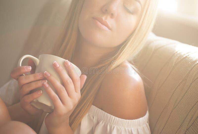 Schöne junge Frau, die am Wohnzimmer beim Genießen im Kaffee sich entspannt lizenzfreie stockfotografie