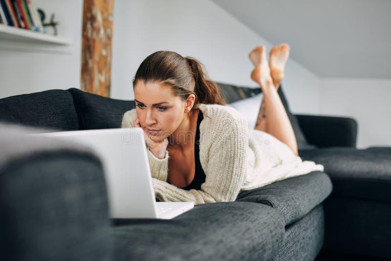Schöne junge Frau, die zu Hause an Laptop arbeitet stockfoto