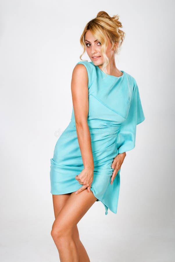 Schöne junge Frau in einem blauen Kleid stockbild