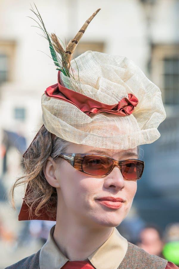 Schöne junge Frau in einem herrlichen Federhut und -Sonnenbrille lizenzfreies stockfoto