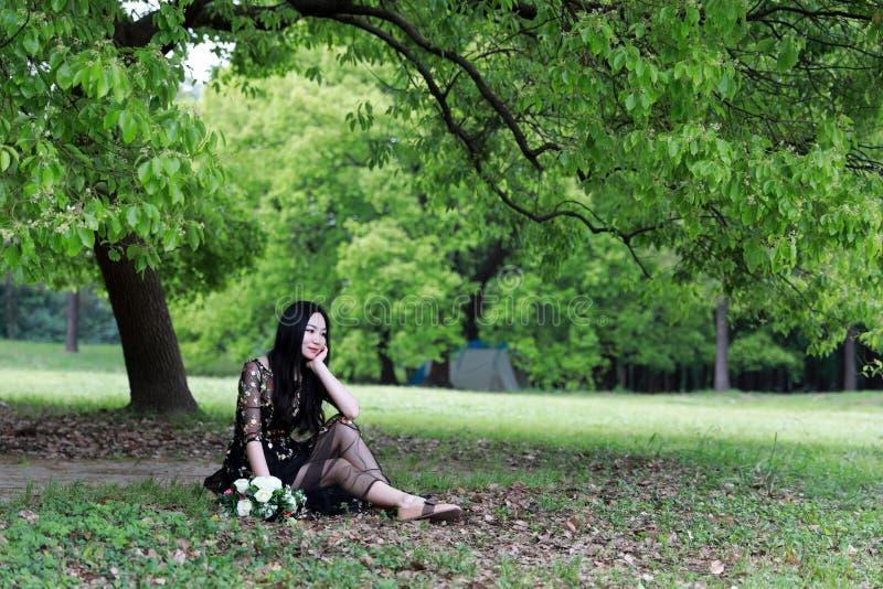 Schöne junge Frau in einem langen dunklen Kleid, das auf Gras unter einem Baum sitzt stockfoto