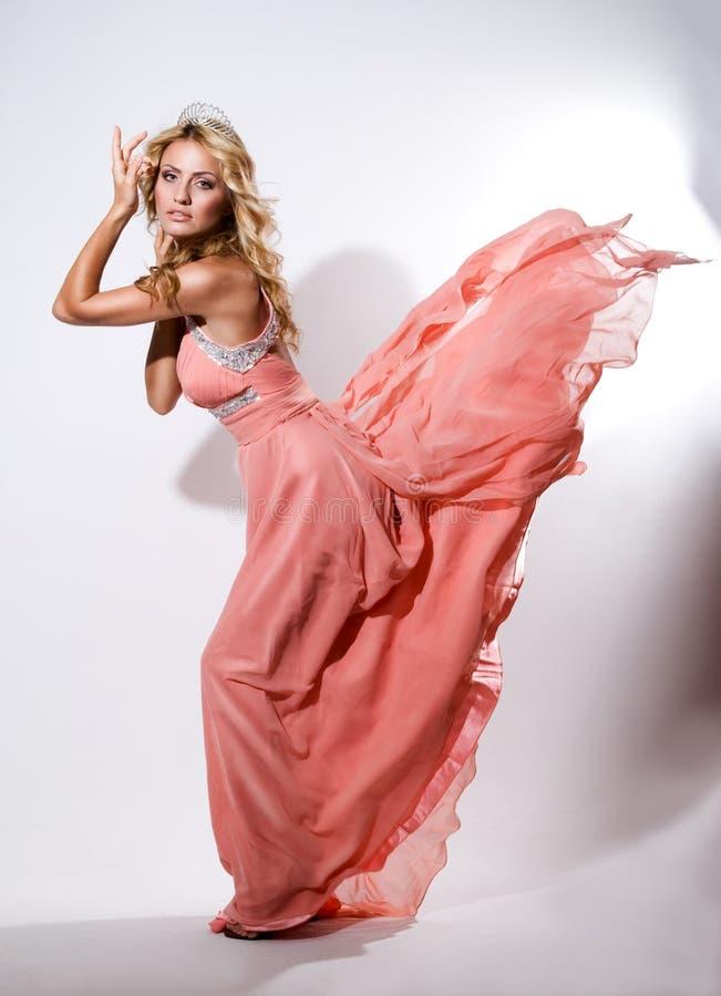 Schöne junge Frau in einem langen rosa Kleid und in einer Krone auf ihrem Kopf lizenzfreie stockbilder