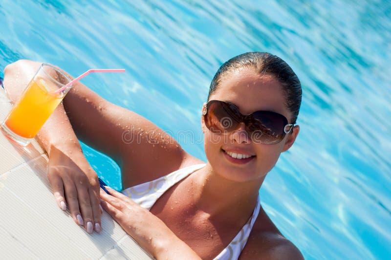 Schöne junge Frau an einem Pool stockfotos