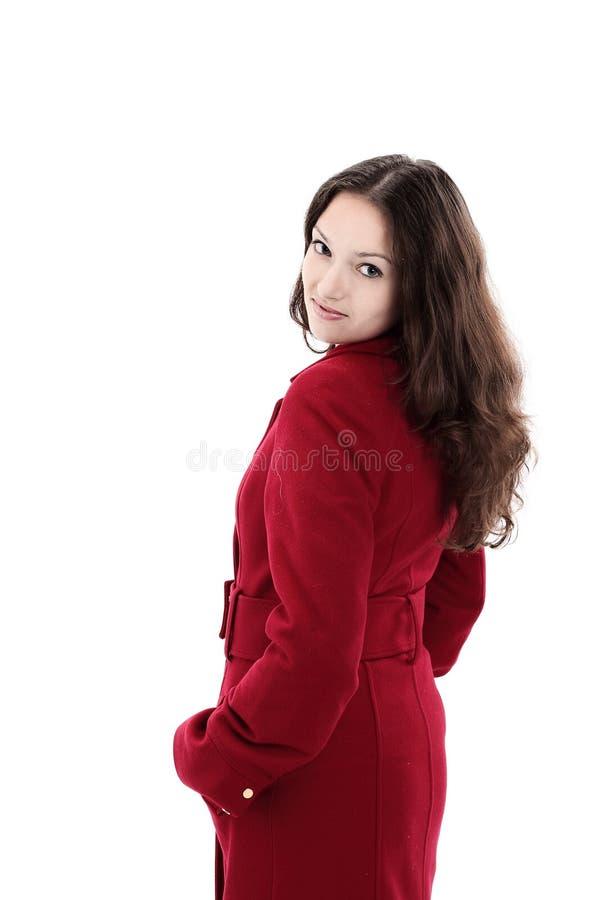 Schöne junge Frau in einem roten Mantel Lokalisiert auf Weiß lizenzfreie stockbilder