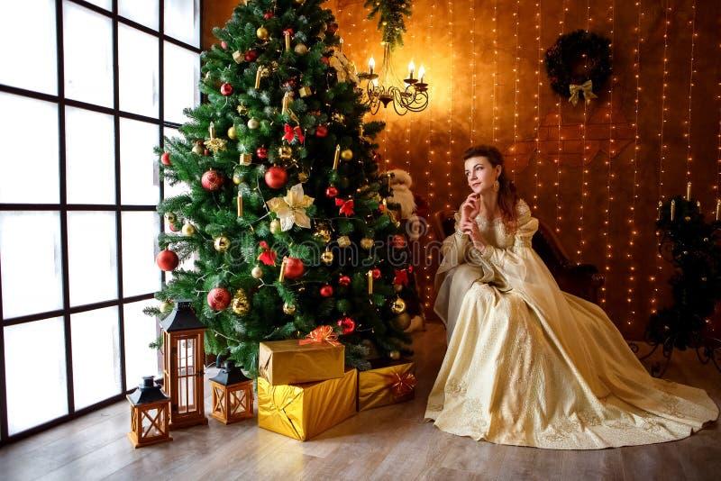 Schöne junge Frau in einem schönen Kleid, das am Weihnachtsbaum mit Geschenken, Weihnachten und neuem Jahr sitzt lizenzfreie stockbilder