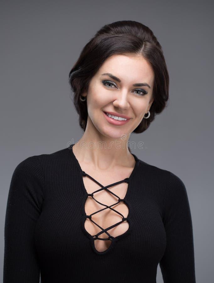 Schöne junge Frau in einem schwarzen Kleid stockbild