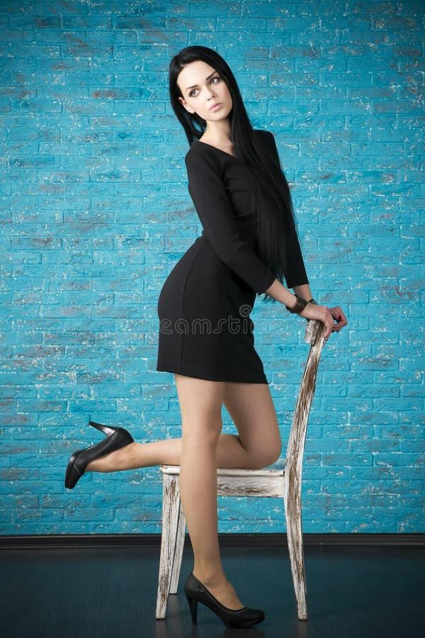 Schöne junge Frau in einem schwarzen Kleid, das gegen den Hintergrund einer blauen Backsteinmauer aufwirft lizenzfreie stockfotos