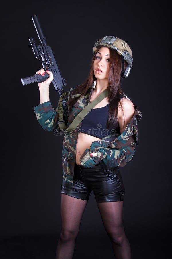 Schöne junge Frau in einer Militäruniform mit einem Submachine GU lizenzfreie stockfotografie