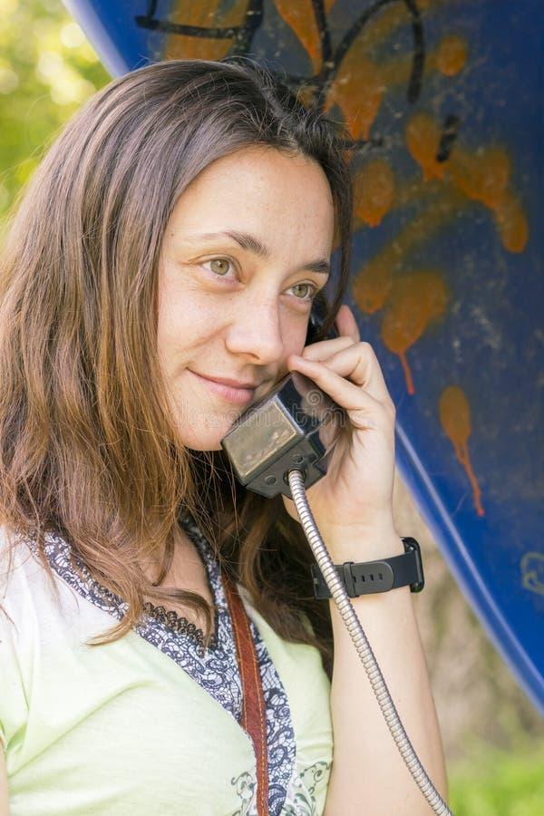 Schöne junge Frau in einer Telefonzelle Das M?dchen spricht am Telefon vom M?nztelefon Frau, die per allgemeines Telefon spricht lizenzfreies stockbild