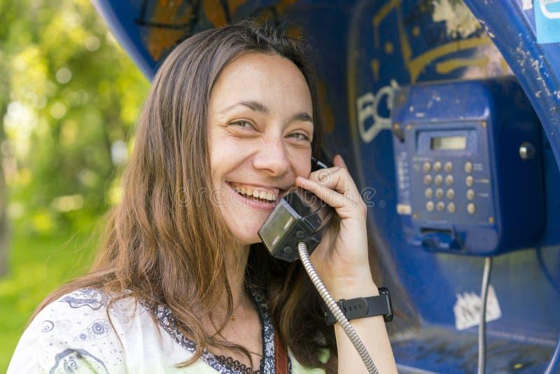 Schöne junge Frau in einer Telefonzelle Das M?dchen spricht am Telefon vom M?nztelefon hübsche Frau, die durch Öffentlichkeit spr lizenzfreie stockbilder