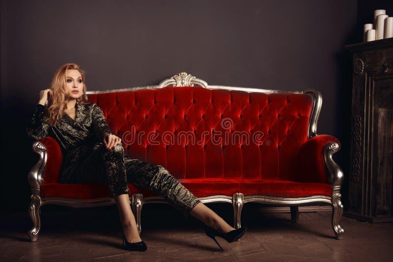 Schöne junge Frau in einer velor Klage sitzt auf einer roten Weinlesecouch lizenzfreie stockfotos