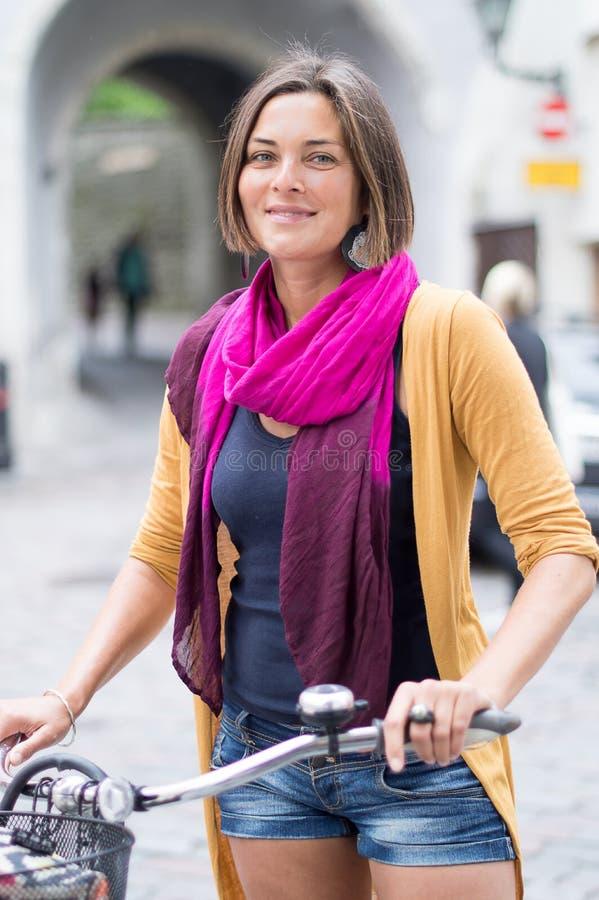 Schöne junge Frau, Fahrrad, Stadt stockfotografie