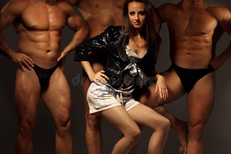 Schöne junge Frau gegen drei Athleten stockbilder