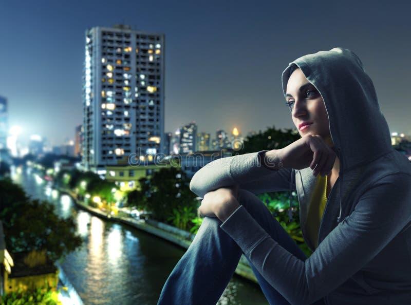 Schöne junge Frau gegen eine Stadt bis zum Nacht stockfoto