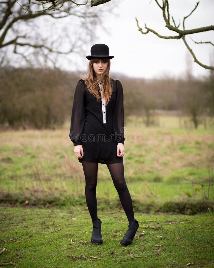 Schöne junge Frau gekleidet in der schwarzen tragenden Melone stockfotos