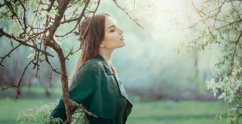 Schöne junge Frau genießt die Natur in einem Garten, Happy Schöne Brunette Mädchen in nebligen Garten mit Bäumen stockbild